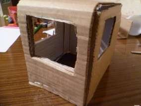 Из картона делаем кабину молоковоза - куб со стороной 13 см*13 см. Намечаем места окон - переднего и боковых. Вырезаем лишний картон.