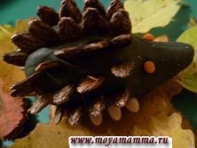 Для изготовления ежика из пластилина серого цвета сформировать тело ежика овальной формы с вытянутым носом. Глазки ежика - из пластилина. Иголки у ежика на спинке из нескольких рядов арбузных семечек.