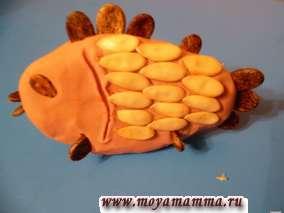 Для рыбки из пластилина формируем овал. Из дынных семячек делаем чешую - семечки слегка продавливаем в пластилин. Из арбузных семечек делаем жабры, плавники и хвостик (семечки втыкаем в пластилин).