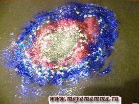 В центре - песок серебристого цвета, вокруг него - песок розового цвета, затем - песок фиолетового цвета.