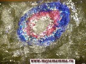 Затем на свободных местах листа бумаги наносим клей мазками и посыпаем песок серебристого цвета в качестве маленьких звездочек и немного маленьких кусочков серебристой фольги в качестве звезд покрупнее.
