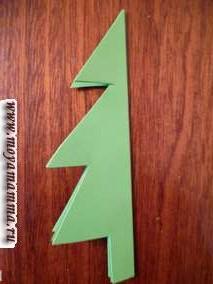 Складываем наши прямоугольники друг с другом и складываем еще раз пополам. Затем вырезаем фигуру в виде половины елки так как показано на фотографии ниже.