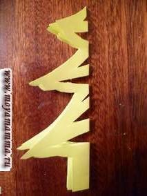 Елку можно вырезать аналогично тому как вырезают снежинки из бумаги. Например, так как показано на фотографии.