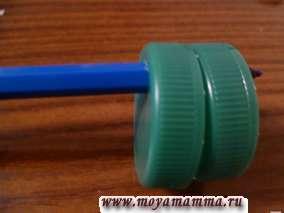 Крышки приставляем друг к другу и делаем сквозное отверстие диаметром, подходящим для фломастера. В отверстие вставляем фломастер. Крышки можно закрепить между собой при помощи скотча.
