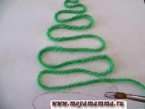 Кисточкой наносим клей ПВА на контур елки и приклеиваем зеленую нить по контуру.