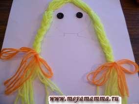 Затем заплетаем принцессе косы. Отрезаем по три полоски оранжевых ниток длиной 20-25 см и закрепляем косы принцессы бантиками.
