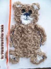 Поделка из шерстяных ниток Медвежонок. Завязываем бантик на шее медвежонка.