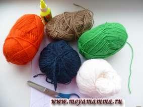 Потребуется лист плотной бумаги; вязальные шерстяные нитки оранжевые, коричневые, темно-синие или черные, белые, зеленые; ножницы, клей ПВА.