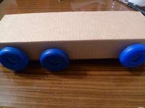 Поделка машина из бутылки. Прорезаем отверстия и вставляем пробки - по три с каждой стороны.