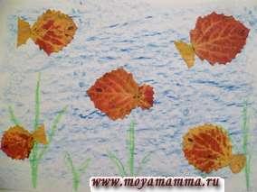 Из осиновых красно-желтых и желто-красных листьев. Фон можно закрасить мелком в синий цвет либо использовать картон синего цвета. Водоросли можно нарисовать зеленым мелком либо наклеить листья ивы.