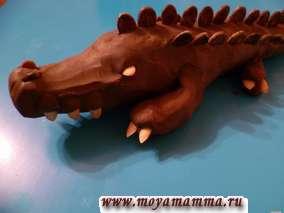 Глаза, зубы, когти на лапах крокодила из семечек дыни. Ноздри крокодила - из арбузных семечек, глубоко вошедших в пластилин. На спине крокодила делаем три ряда арбузных семечек. При этом в крайних рядах арбузные семечки пониже, чем в центральном ряду.