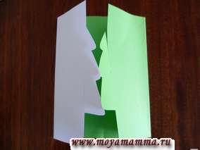 Делаем надрезы у елочек таким образом : у одной - сверху , у другой - снизу доходя до середины елочки . Вставляем елочку одну в другую. Листы бумаги отгибаем и складываем их друг с другом, скрепляем степлером либо клеем.