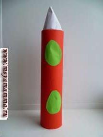 Для изготовления объемной ракеты сделан цилиндр из бумаги красного цвета. Сверху ракету венчает конус, который скручен из треугольника белого цвета.