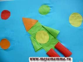 Следующая аппликация выглядит объемной. Так как крылья ракеты изготовлены из конусов, которые скручены из треугольников. Ступени ракеты изготовлены из цилиндров, которые скручены из прямоугольников. Для планет выбрана бумага разных цветов. Вся аппликация выполнена на листе формата А4 темно-голубого цвета.