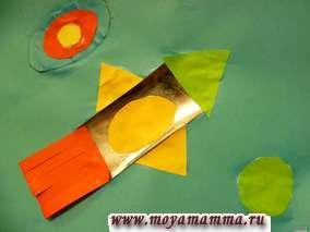 Еще один вариант ракеты в космосе. Корпус ракеты выполнен из фольги стального цвета. Для придания небольшого объема пламя ракеты изготовлено из полосок красного цвета приклеенных только за край.