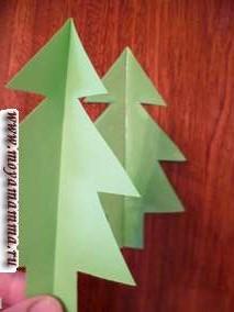 Новогодняя елка из бумаги своими руками. Наносим клей сверху на наши верхние половинки елок.