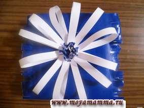 прикрепление белого цветка к синей сумке