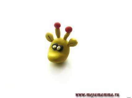на верхушке головы создадим рожки из желтого и красного пластилина. А вот для глаз используем белый и черный цвет материала.