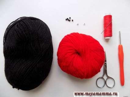 Пряжа красного и черного цвета и крючок для вязания божьей коровки