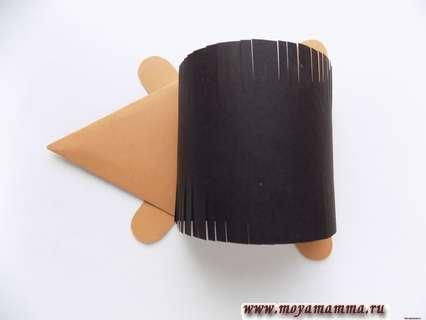 Из части коричневой бумаги вырезаем лапки ежику и приклеиваем их по бокам