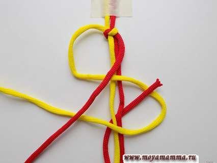 Красный шнур провести под основанием, а затем вывести через петлю, получившуюся справа.