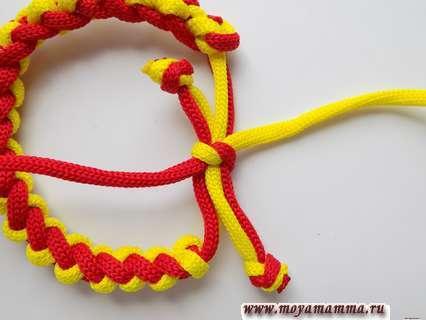 Браслет из двух шнуров. Концы перевязываем двухцветной заготовкой, делая обычный узел.