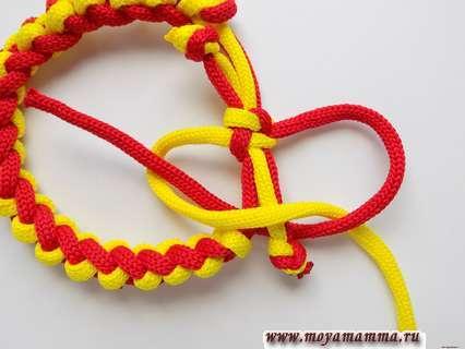 Браслет из двух шнуров. Красный конец шнура через желтую петлю.