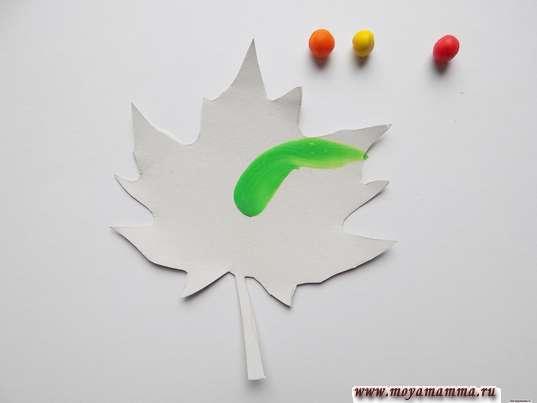 Размазывание зеленого шарика из пластилина