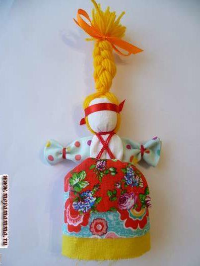 Кукла Веснянка. Завязывание красной ленты на голове в качестве очелья