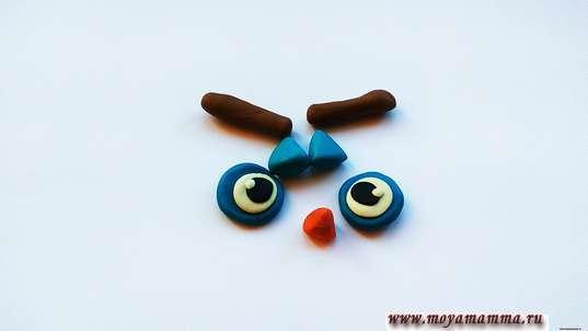 Сова из природного материала. Глаза, используя круглые лепешки трех цветов, оранжевый клюв, уши и коричневые черточки-брови