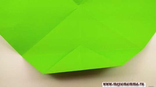 В этом месте нужно сформировать складку. Разложите уголок и согните треугольник пополам.