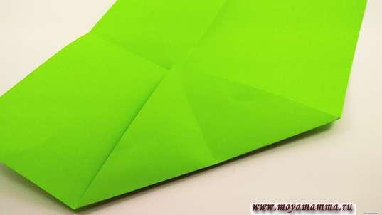 Противоположный нижний угол по намеченным линиям согните, выделяя равнобедренный треугольник.