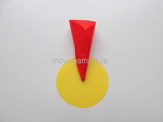 Круг, вырезанный из желтой бумаги с лепестком
