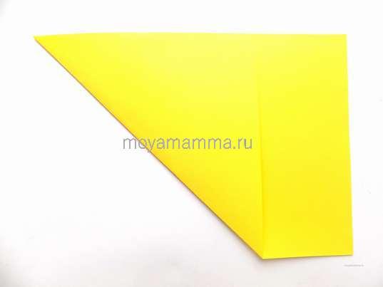 Загибание угла листа желтой бумаги.