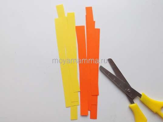 Новогодние поделки. Несколько узких полосок из бумаги оранжевого и желтого цвета.